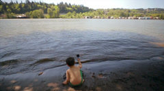 (View From Behind) Little Boy Sits Close To Water And Plays With Sand Toys Stock Footage