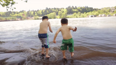 Two Little Asian Boys Jump And Splash In Waves Stock Footage