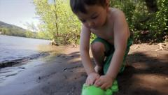 Cute Little Asian Boy Plays With A Sand Toy By The Shoreline Stock Footage