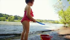 Cute Asian Girl, In Pink Swimsuit, Plays With Her Sand Toys By The Water's Edge Stock Footage