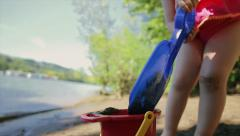 Closeup Of Bucket, Little Girl Pours Wet Sand Into It With Her Large Blue Shovel Stock Footage