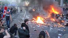Man running over burning debris at riot - HD 1080p Stock Footage