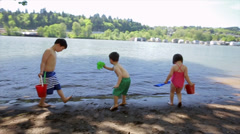 Group Of Multi-Ethnic Kids Play In Gentle Waves With Their Sand Toys - stock footage