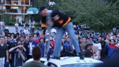 Rioter kicks and destroy police car light-bar Stock Footage
