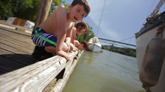 Curious Kids Sit At The Edge Of A Dock And Look Into Water, One Smiles At Camera Stock Footage