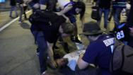 Stock Video Footage of Unconscious man attended by crowd of rioters