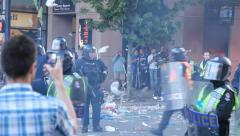 Small tornado of debris fly around riot officers Stock Footage