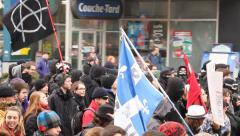Masked anarchists protesters walking with flag - stock footage