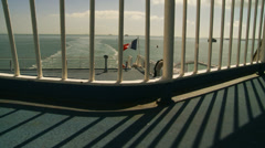 French flag through railings on ferry (dolly & zoom) Stock Footage