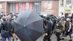 Anarchist demonstrators hide their faces with umbrella - stock footage