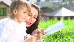 Mother with her baby reading the book outdoors. Slow-mo 240 fps. Full HD 1080p Stock Footage