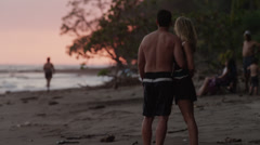 Costa Rica, Esterillos Beach, Two couples on beach, one is kissing Stock Footage