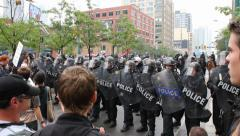 Police officers in line block demonstrators at busy corner Stock Footage