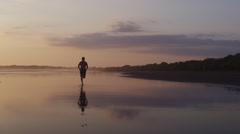 Costa Rica, Esterillos Beach, Man running on beach at sunset Stock Footage