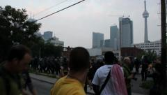 Police officers in riot gear walking with CN Tower in background Stock Footage