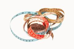Three coiled tape measures in blue red and yellow Stock Photos