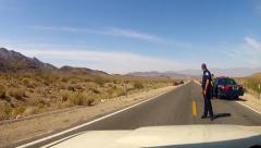 POV Car Passing State Troopers Working Traffic Stop On Desert Hwy Stock Footage