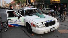 Young people walk around abandoned police car with graffiti Stock Footage