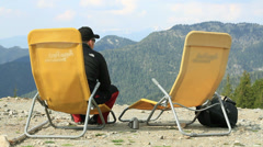 Male hiker sitting and relaxing at the summit enjoying hot drink HD Stock Footage