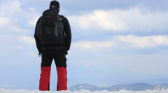 Man at the snowy mountain peak looking at beautiful view HD Stock Footage