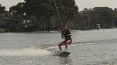 USA, Florida, Orlando, Maitland Lake, Woman jumping on wakeboard Stock Footage