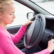 Female car driver starting the engine. Kuvituskuvat