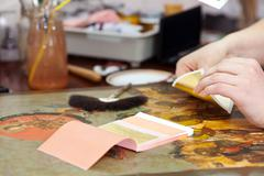 Restorer gilding on the old icon - stock photo
