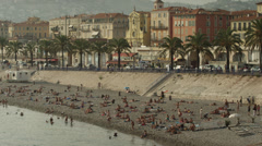 Pan up of people enjoying the Promenade des Anglais / Nice, France - stock footage