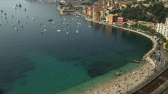 Panning shot of people on beach and moored boats / Villafranche, France - stock footage