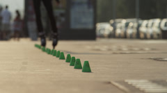 Medium shot of man on rollerblades weaving through cones / Nice, France Stock Footage