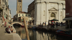 Medium shot of people along Venetian canal / Venice, Italy - stock footage
