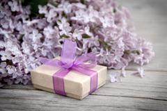gift box with purple bow and lilac on wood - stock photo