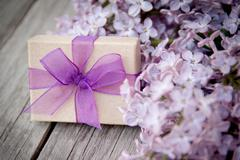 Gift box with purple bow and lilac on wood Stock Photos