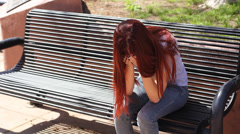 Girl cries on bench Stock Footage