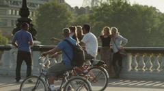 Medium shot of person taking photograph of tourists on bridge / Paris, France Stock Footage