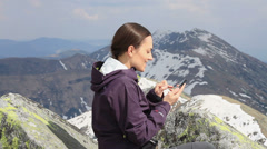 Woman texting on her mobile phone in the mountains HD Arkistovideo