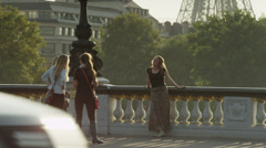 Medium shot of woman taking photograph of friend on bridge / Paris, France Stock Footage