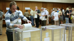 Young man puts electoral billeting in the ballot box - stock footage