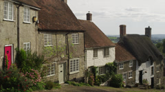 Medium shot of thatched-roofed houses in English village / Gold Hill, Stock Footage