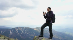 Woman texting on her mobile phone in the mountains HD Stock Footage