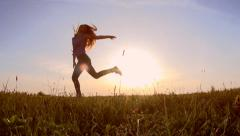 Beauty teen girl jumping over sunset sky. Slow-mo. 1080p full HD Stock Footage