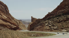 Medium shot of cars driving between large rock formations on Interstate 70 Stock Footage