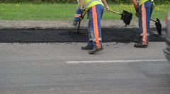Workers shovels special tools leveling hot asphalt road hole Stock Footage
