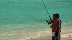 Fishermen catch fish on a fishing rod on the sea sandy shore Stock Footage