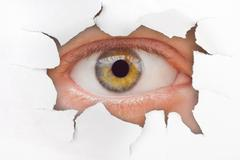 Eye looking through hole on paper Stock Photos