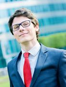 outdoor portrait of a dynamic junior executive smiling - stock photo