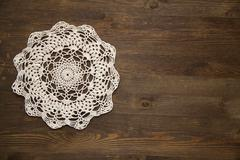 Crochet doily over dark wood - stock photo