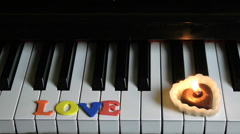 Stock Video Footage of Love on Piano Keys and Candle Light