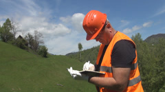 Stock Video Footage of Engineer taking notes, calculate, making plans for a new construction.