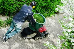 gardener mowing the lawn in a park - stock photo